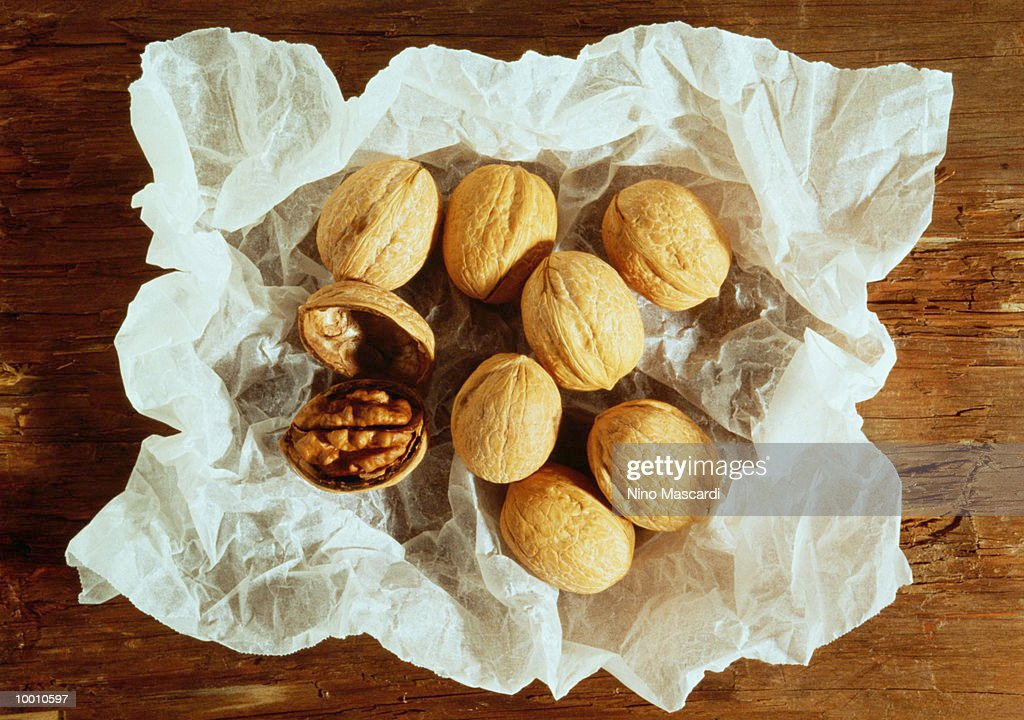 WALNUTS ON WHITE CRUMPLED PAPER : Stock Photo