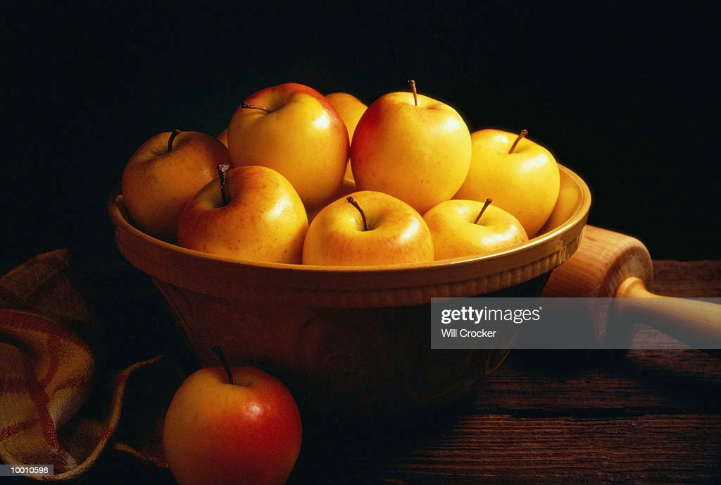 YELLOW APPLES IN BOWL BY ROLLING PIN : Foto de stock