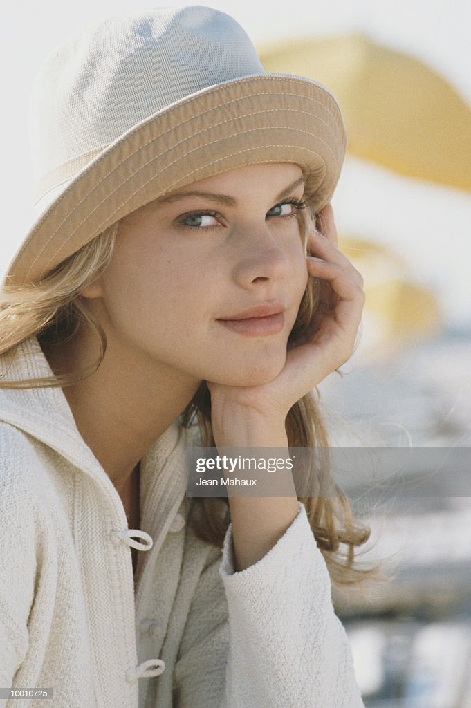 YOUNG WOMAN IN HAT WITH CHIN ON HAND : Stock Photo