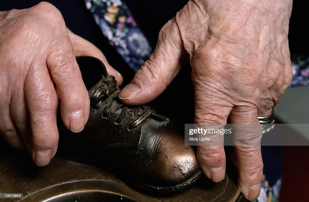 MATURE WOMAN'S HANDS WITH BRONZED BABY SHOES : Stock Photo