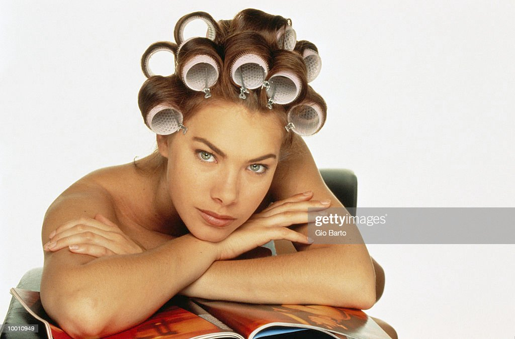 BARE SHOULDERED WOMAN WITH CURLERS IN HAIR : Stock-Foto