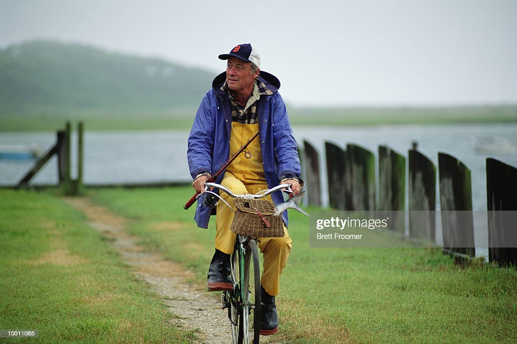 MATURE MAN WITH FISHING GEAR ON BICYLCLE : Foto de stock