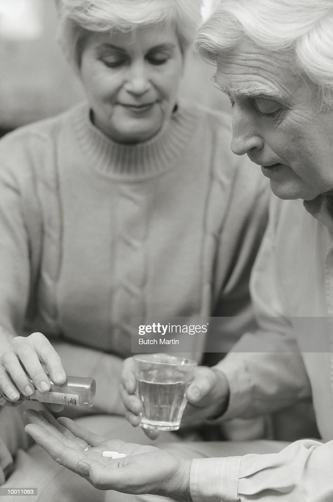 MATURE WOMAN GIVING MAN HIS MEDICATION : Stock Photo