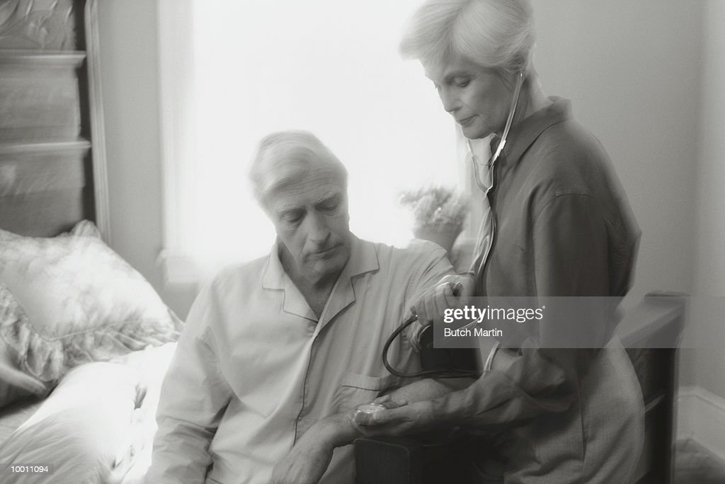 MATURE WOMAN TAKING MAN'S BLOOD PRESSURE : Stock Photo