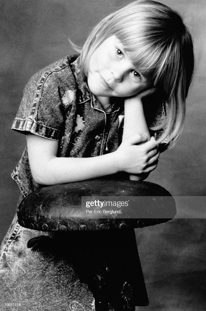 PORTRAIT OF A GIRL LEANING ON STOOL : Foto de stock