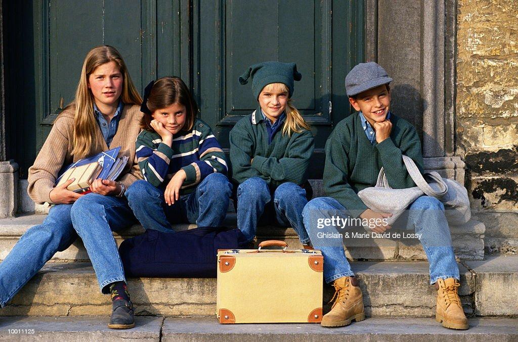 CHILDREN ON DOORSTEP WITH OVERNIGHT BAGS : Foto de stock