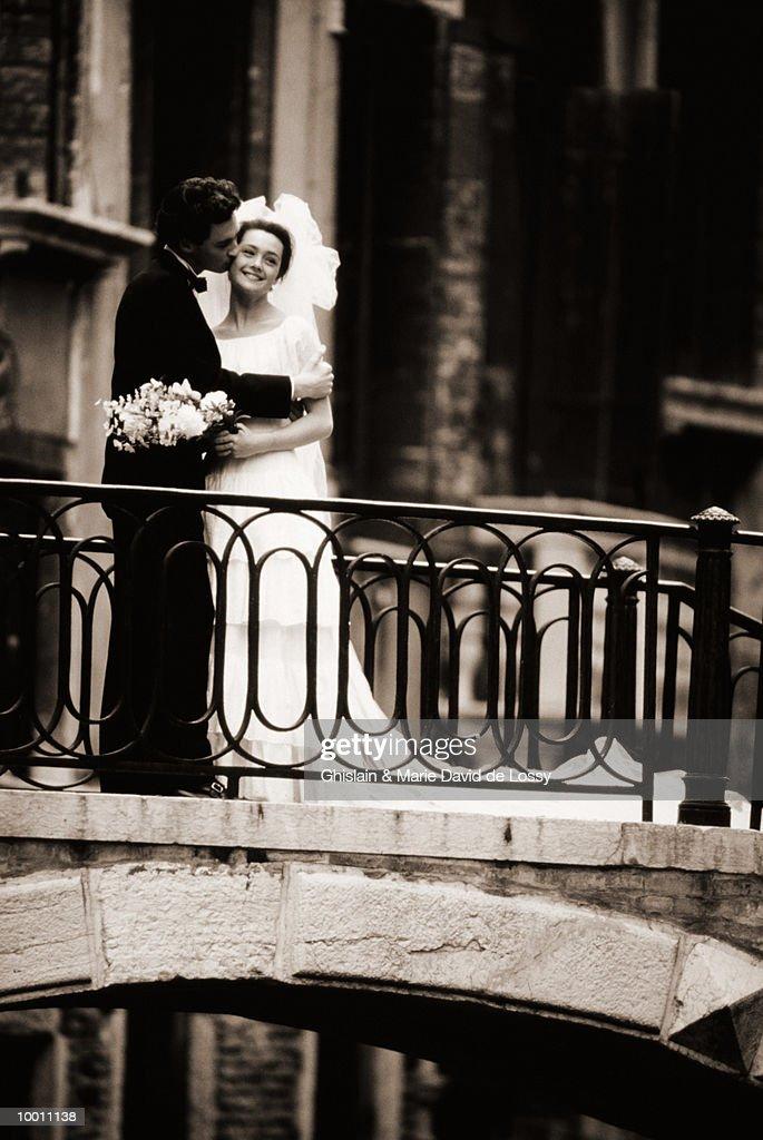 GROOM KISSING BRIDE ON BRIDGE IN VENICE : Foto de stock