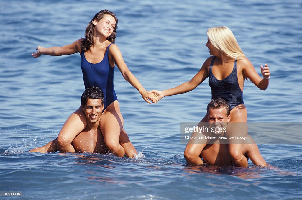 WOMEN ON MEN'S SHOULDERS IN OCEAN : Stock Photo
