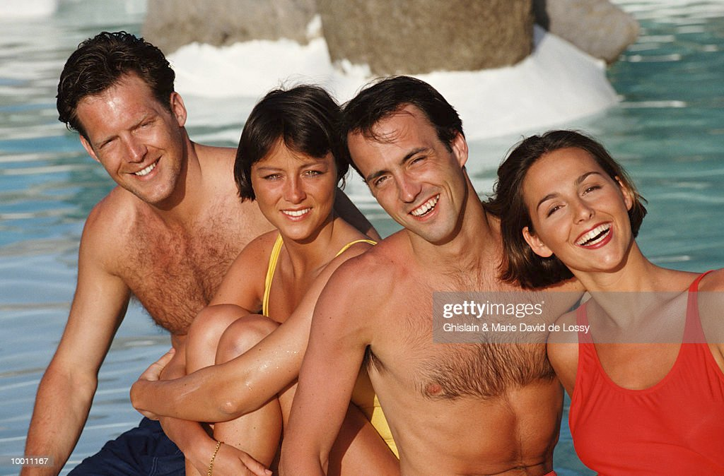 SMILING COUPLES RELAXING BY POOL : Stock-Foto