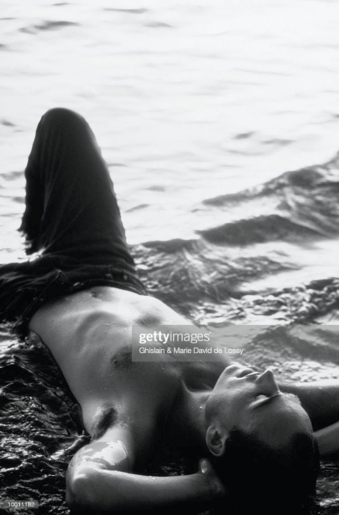 YOUNG MAN LYING IN SURF IN BLACK AND WHITE : Stock-Foto