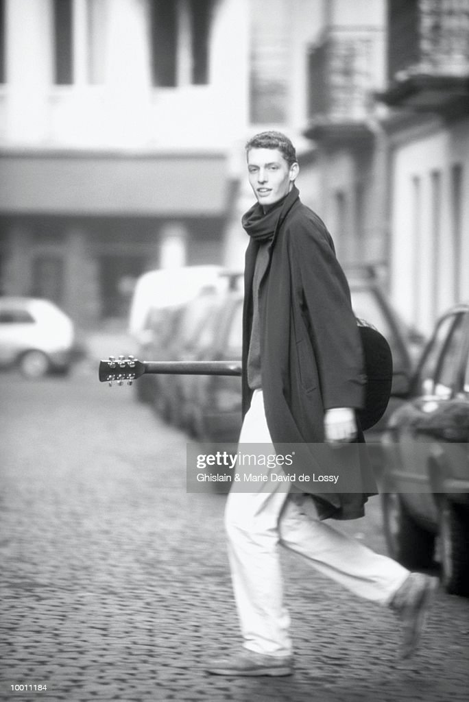 YOUNG MAN WITH GUITAR CROSSING STREET IN BLACK AND WHITE : Stock Photo