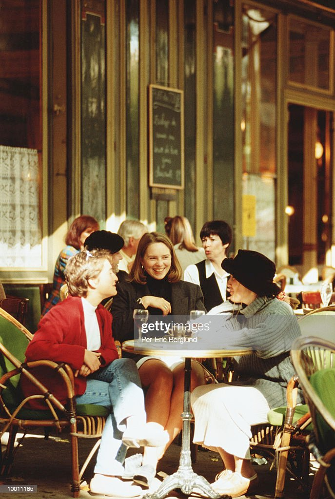 WOMEN ENJOYING DRINKS AT OUTDOOR CAFE : Stock Photo