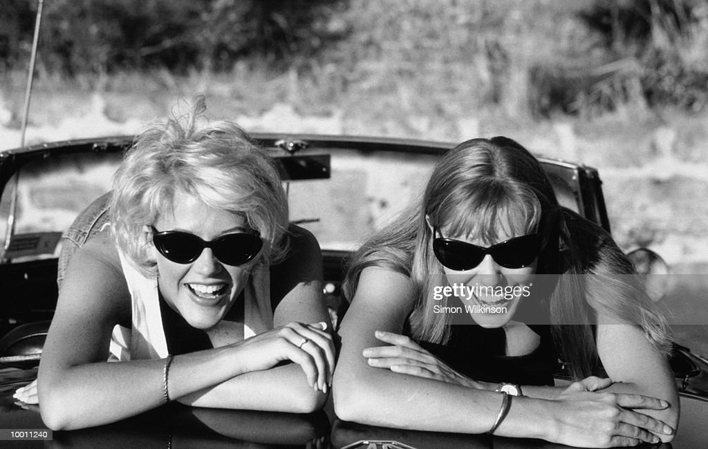 YOUNG WOMEN ON BACK OF MG CONVERTIBLE IN BLACK AND WHITE : Stock Photo