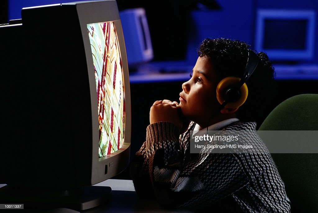 YOUNG BOY AT COMPUTER WITH HEADPHONES : Stock Photo