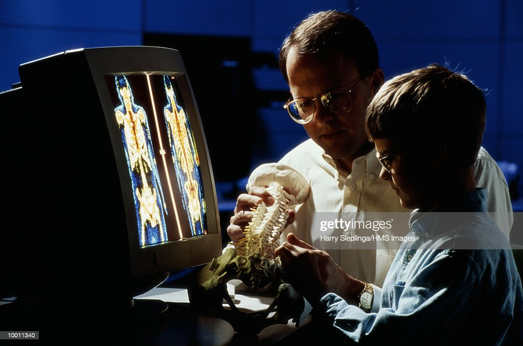 BOY & MAN AT COMPUTER WITH HUMAN BONE REPLICA : Foto de stock