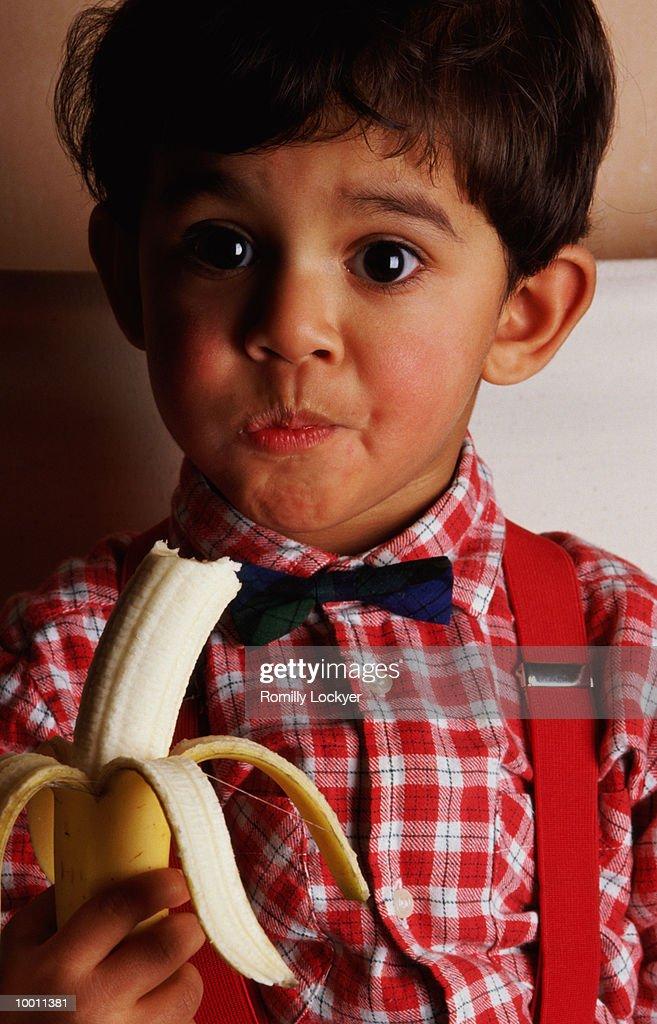 YOUNG BOY EATING BANANA : Foto de stock