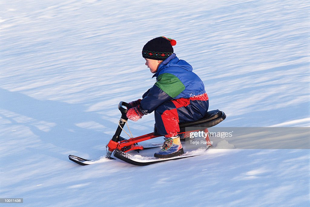 BOY SLEDDING DOWN SNOW COVERED HILL : Stock Photo