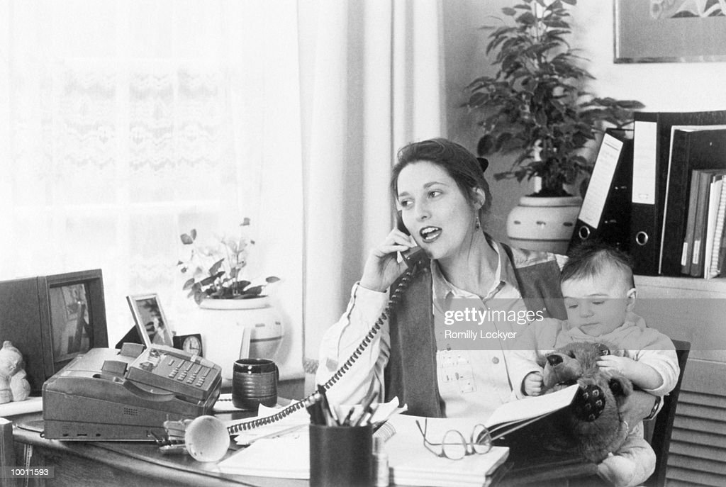MOTHER ON HOME OFFICE PHONE & HOLDING BABY : Stock Photo