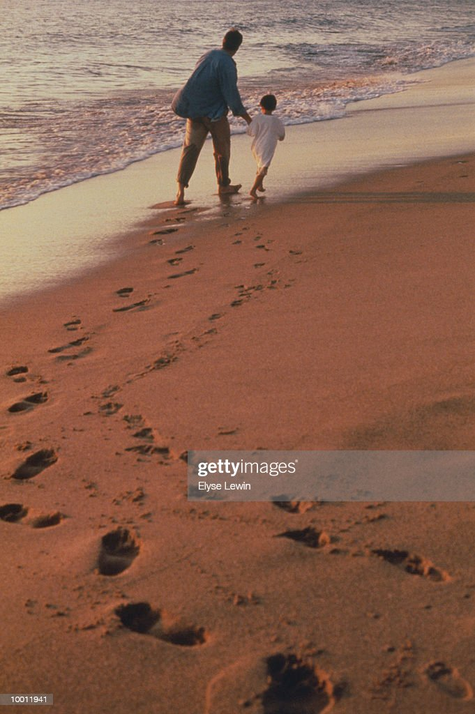 FATHER & SON WALKING ON BEACH WITH FOOTPRINTS : Stock Photo