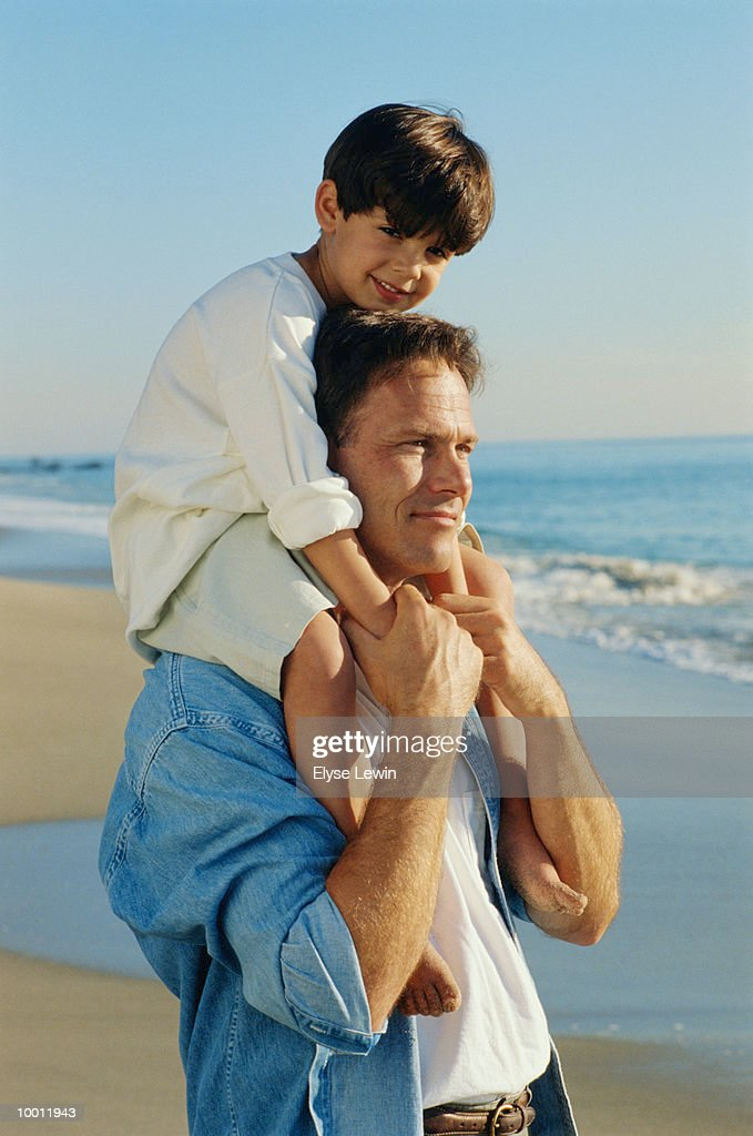 SON ON FATHER'S SHOULDERS AT BEACH : Stock Photo
