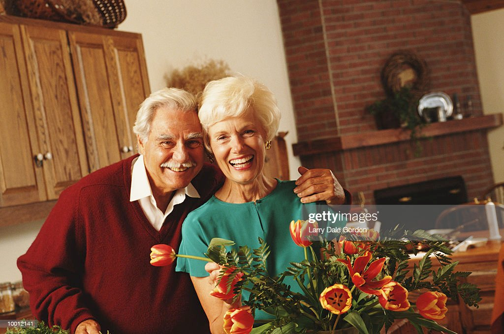 PORTRAIT OF A MATURE COUPLE IN HOME WITH FLOWERS : Stock Photo