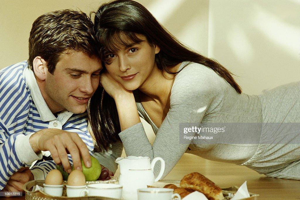 COUPLE HAVING BREAKFAST ON FLOOR : Stock Photo