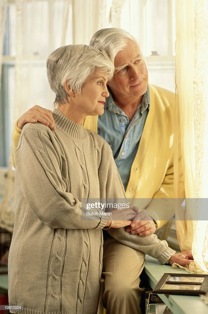 MATURE COUPLE LOOKING OUT WINDOW IN HOME : Foto de stock