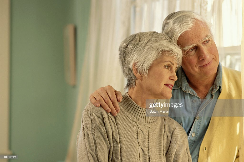 MATURE COUPLE LOOKING OUT WINDOW : Stock Photo