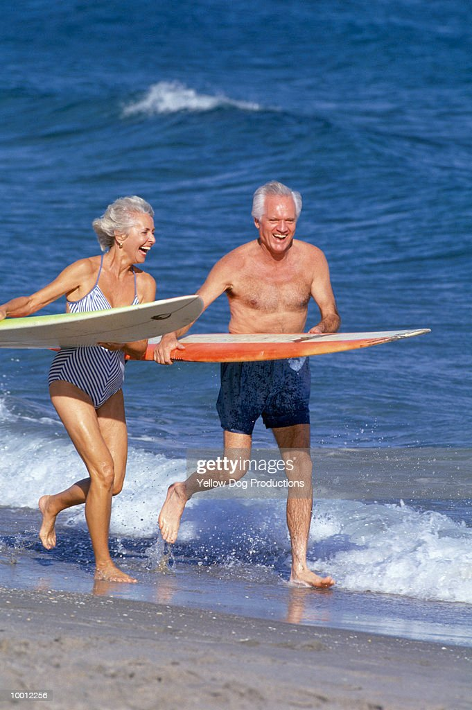 MATURE COUPLE WITH SURFBOARDS ON BEACH : Foto de stock