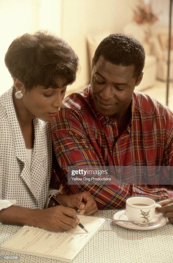 BLACK COUPLE WITH COFFEE & CHECKBOOK : Stock Photo
