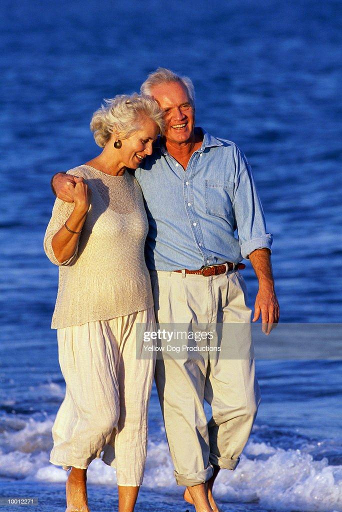 MATURE COUPLE WALKING ON BEACH : Stock Photo