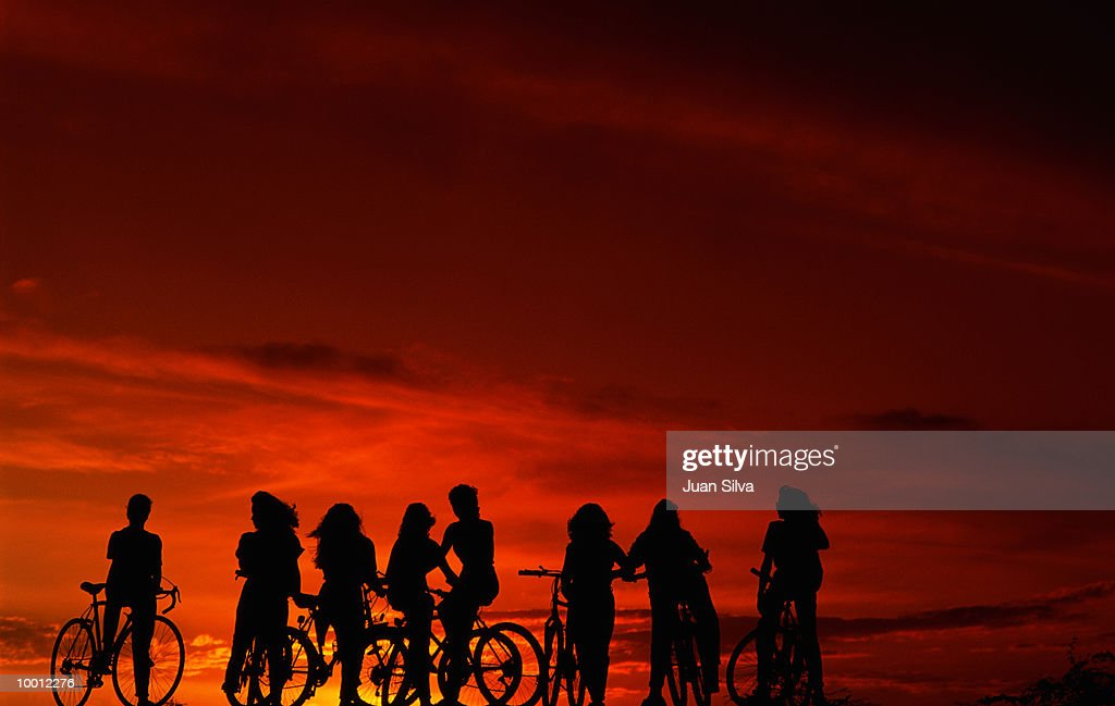 SILHOUETTE OF TEENAGERS ON BICYCLES AT SUNSET : Foto de stock
