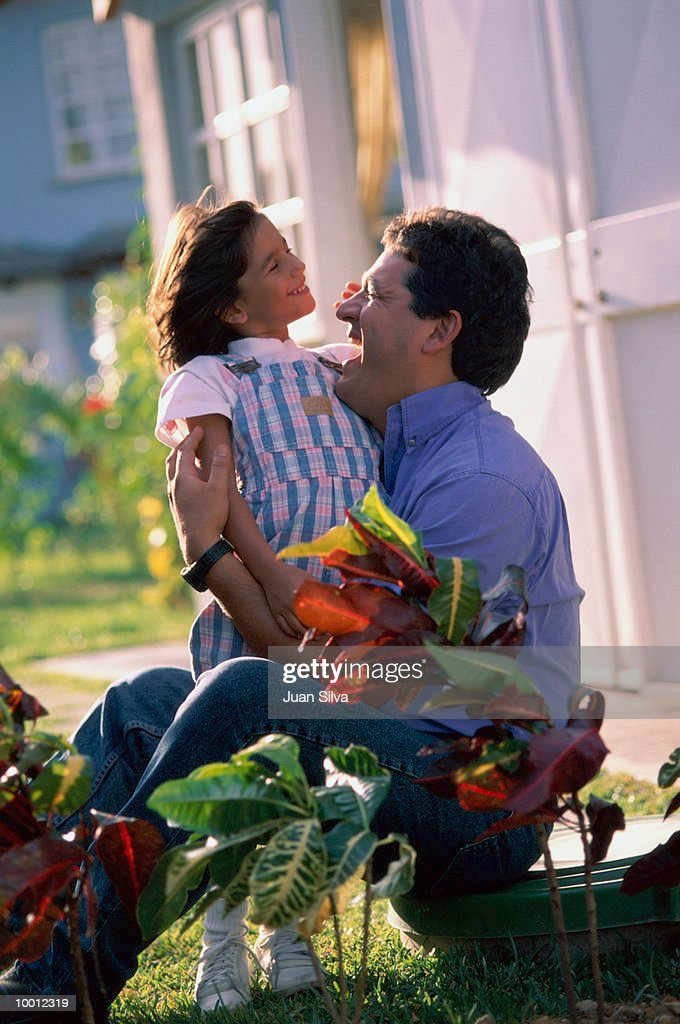 FATHER PLAYING WITH DAUGHTER IN GARDEN : Stock-Foto