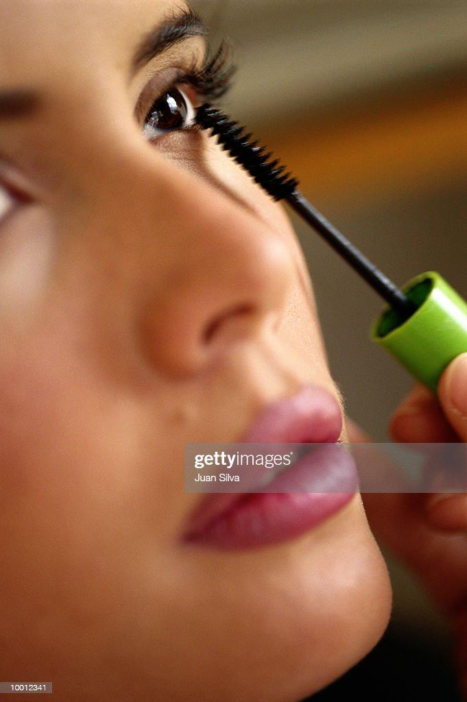 CLOSE-UP OF A WOMAN APPLYING MASCARA : Stock Photo