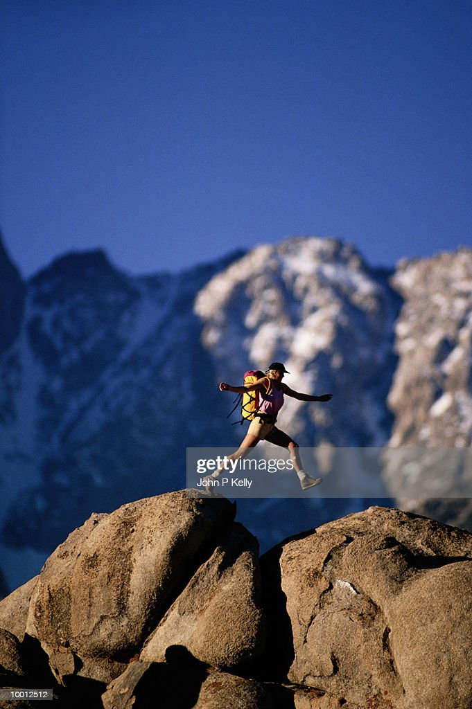FEMALE HIKER JUMPING ROCKS IN THE SIERRAS OF CALIFORNIA : Stock Photo