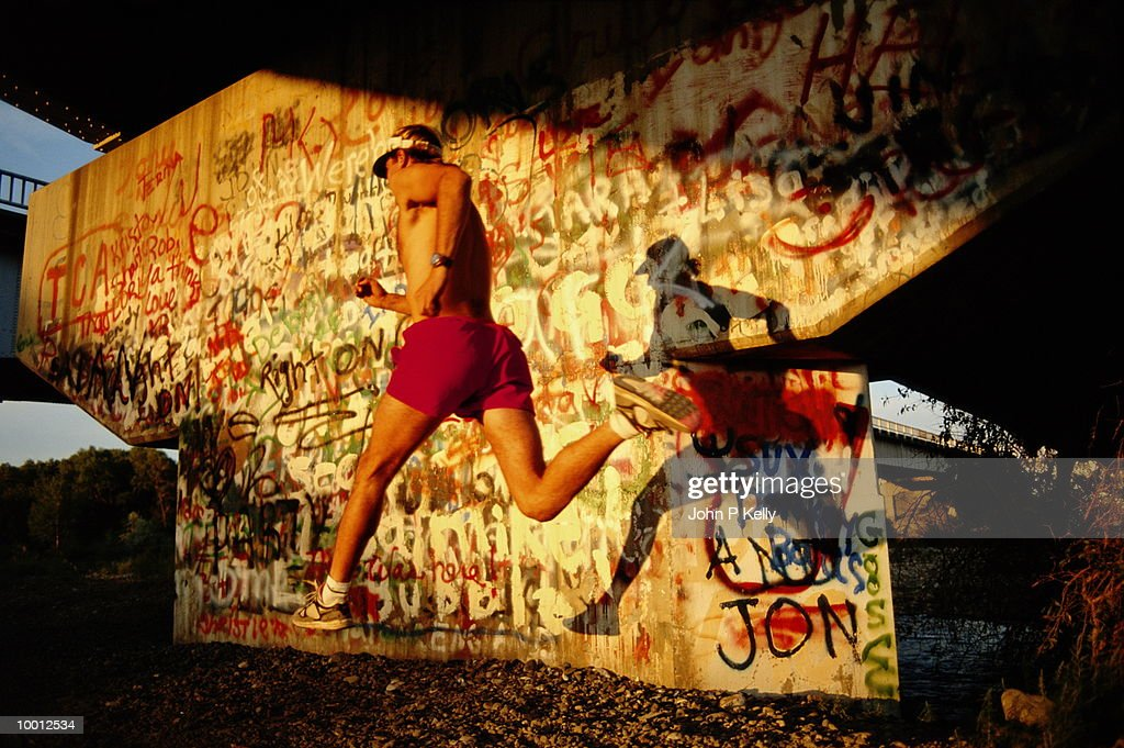MAN RUNNING BY GRAFFITI BRIDGE WALL : Stock Photo
