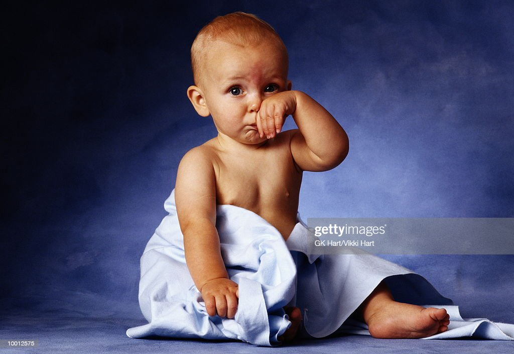 SAD BABY WITH BLANKET & HAND TO FACE : Stock Photo