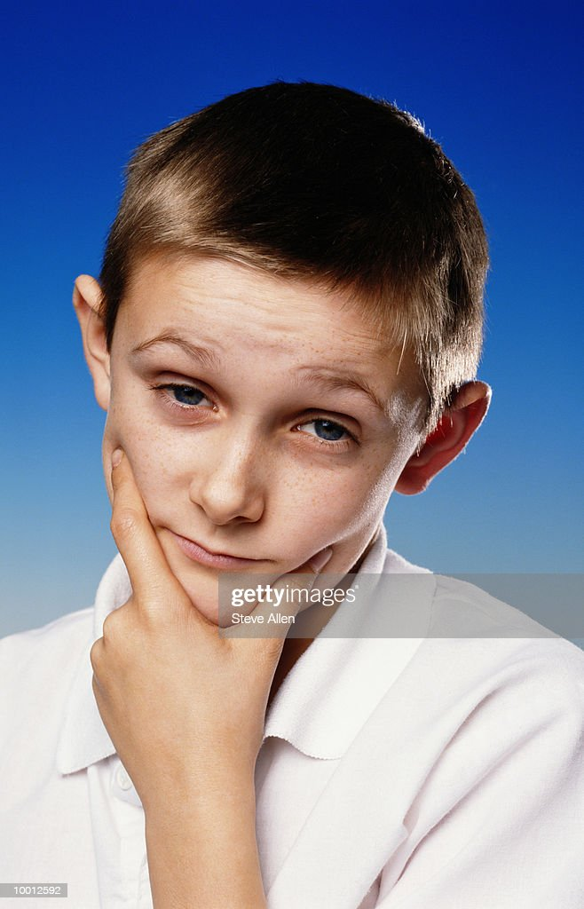 BOY PONDERING THOUGHT WITH CHIN IN HAND : Foto de stock