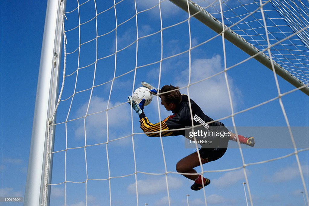 GOALIE IN MIDAIR CATCHING SOCCER BALL : Stock Photo