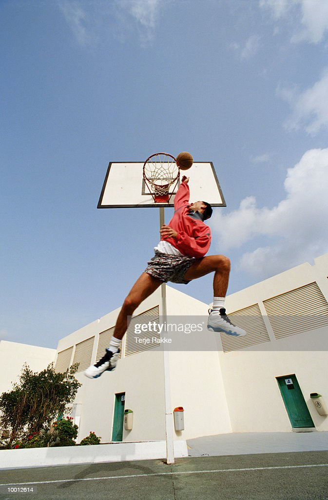 MAN IN MIDAIR PLAYING BASKETBALL : Stock-Foto