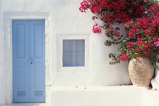 HOME EXTERIOR WITH BLUE DOOR & FLOWERS IN GREECE