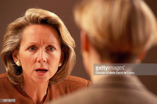 WOMAN TALKING W/STERN FACE TO CO-WORKER