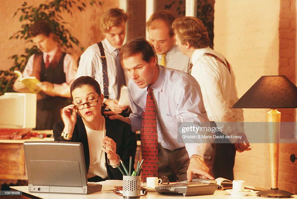 BUSINESSMAN AT DESK BY CO-WORKER : Stockfoto