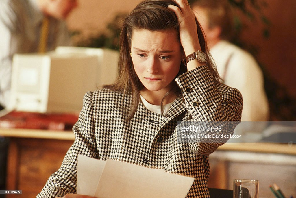 STRESSED BUSINESSWOMAN LOOKING AT PAPERS : Photo