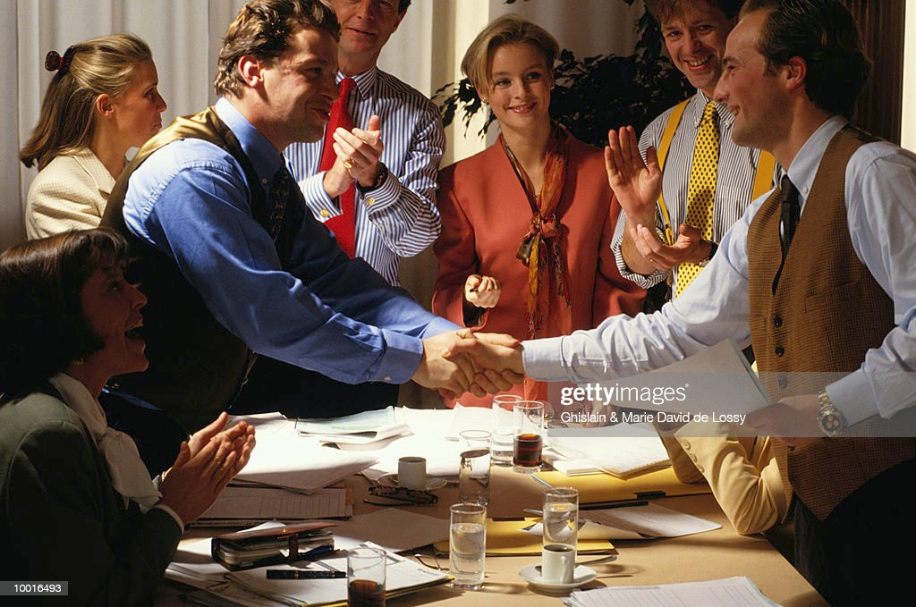 WORKERS SHAKING HANDS OVER CONFERENCE TABLE : Bildbanksbilder