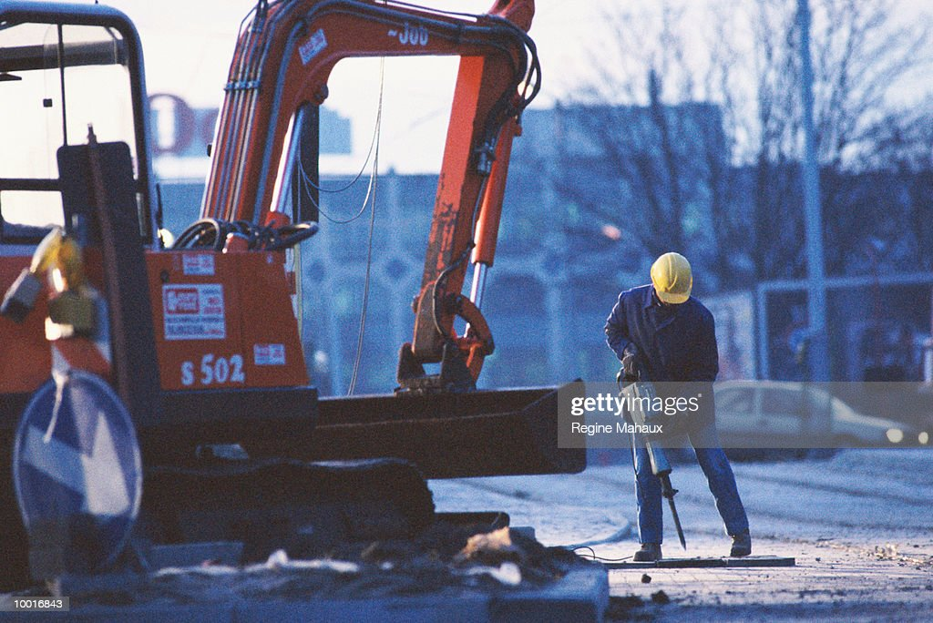 CONSTRUCTION WORKER WITH MACHINERY : Stock Photo