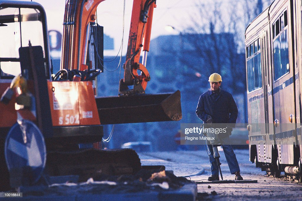 CONSTRUCTION WORKER WITH MACHINERY : Stockfoto