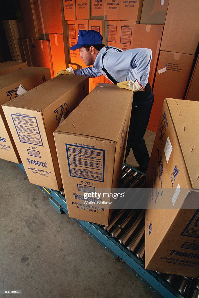 WORKER WITH BOXES IN FURNITURE WAREHOUSE : Stockfoto