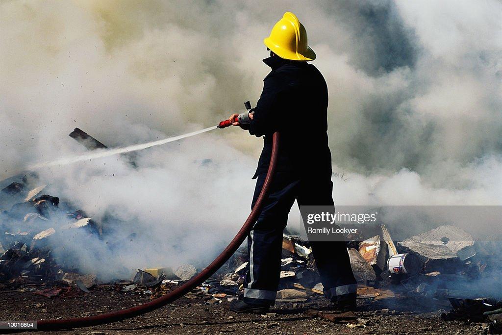 FIREMAN HOSING FIRE IN UNITED KINGDOM : Bildbanksbilder