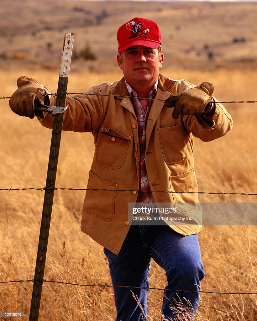 PORTRAIT OF A RANCHER AT FENCE IN EAST OREGON : Stock Photo